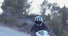 Man riding a sports motorbike at high speed on a curved countryside road