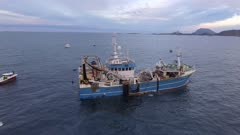 Fishing trawler with Orcas checking the net in North atlantic, Norway, 4K aerial circular movement