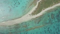 aerial drone circling coral sand cay peninsula