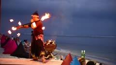 Fire dancer on a beach at sunset