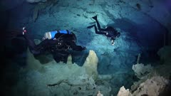 Cave divers exploring underwater cave system in Yucatan, Mexico