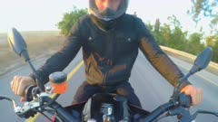 Man riding a sports motorcycle on a curved road