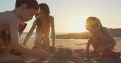 Three kids playing on the beach, eating watermelons and building sand castles