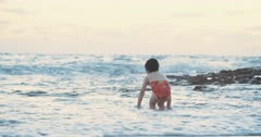 Little girl playing with the waves at the beach during sunset