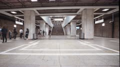 Time Lapse of busy metro station with people boarding trains and escalators