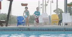 Children having fun jumping and swimming in a swimming pool