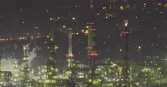 Nighttime view of a large oil refinery with smoke and air pollution rising