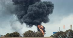 Environmental pollution - huge fire accident in an oil refinery with thick black smoke rising