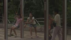 Girl Pushing Two kids on a Swing Set