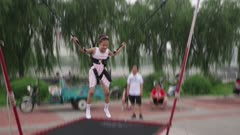 Girl Jumps on bungee trampoline in city plaza