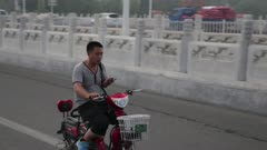 Man talks on phone while on a motorized scooter