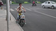 Woman rides motorized scooter with child in her lap