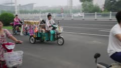 A man on a 3 wheel vending motorcycle stops at traffic light