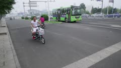 Man waves while on his motorizes scooter with daughter