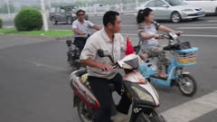 Man on motorized scooter stops at traffic light