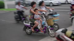 Woman rides motorized scooter with her cild in her lap