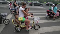 Woman on bike with two children