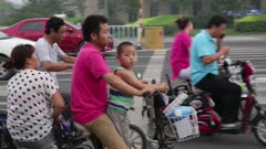 Man rides motorized scooter with child and wife