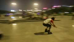 Rollerbladers jump over seated person