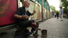 Blind one man band street performer plays banhu & temple block