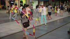 Woman waves rainbow wand with ribbon