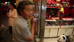 old woman stands infront of street shop