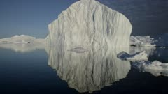 POV on water passing icebergs with glassy water reflection