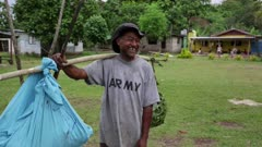 Man smiles wearing an army t-shirt, holding a stick with a bag hanging on it
