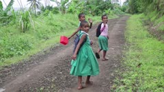 Three kids walk away from camera on dirt road, they wave