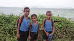 Three kids pose for camera, ocean in the background