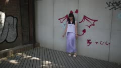 Woman poses for picture against demon graffitti backdrop