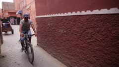Man and child ride bicycles down narrow alley - Handheld