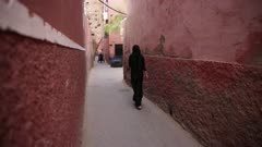 Woman walks down narrow alley - Handheld