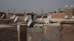 Satellite dishes line the tops of buildings - Handheld