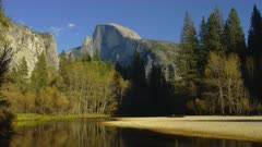 Half Dome and the Merced river with leaves falling in foreground