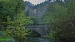 Multnomah Falls with trees and bridge in foreground