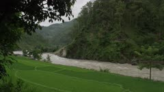 Barabise, Nepal - July 31, 2015: Rice fields, muddy river in spate