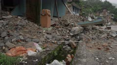 Barabise, Nepal - July 31, 2015: Slow tilt up destroyed house to people on first floor