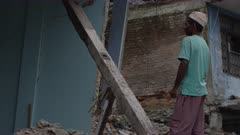 Barabise, Nepal - July 31, 2015: Man stands in front of destroyed house