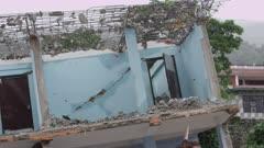 Barabise, Nepal - July 31, 2015: Tilt down destroyed blue house to two men on ground floor