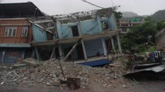 Barabise, Nepal - July 31, 2015: WS destroyed blue house at an angle, three people in house