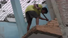 Barabise, Nepal - July 31, 2015: Man shovels rubble from destroyed house