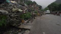 Barabise, Nepal - July 31, 2015: Buses travel along destroyed street