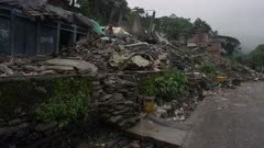Barabise, Nepal - July 31, 2015: Child walks over rubble in destroyed street to water pipe