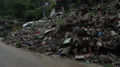 Barabise, Nepal - July 31, 2015: Street with houses turned to rubble, motorbike passes