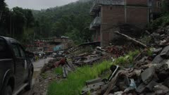 Barabise, Nepal - July 31, 2015: Street with houses turned to rubble, vehicles pass