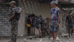 Pokhara, Nepal - August 2, 2015: Soldiers look in windows of destroyed house