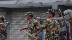 Pokhara, Nepal - August 2, 2015: CU soldiers with tools outside destroyed house