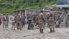 Pokhara, Nepal - August 2, 2015: Group of soldiers with tools in front of destroyed house