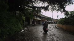 Nepal - August 3, 2015: Motorbike drives along muddy road in front of houses